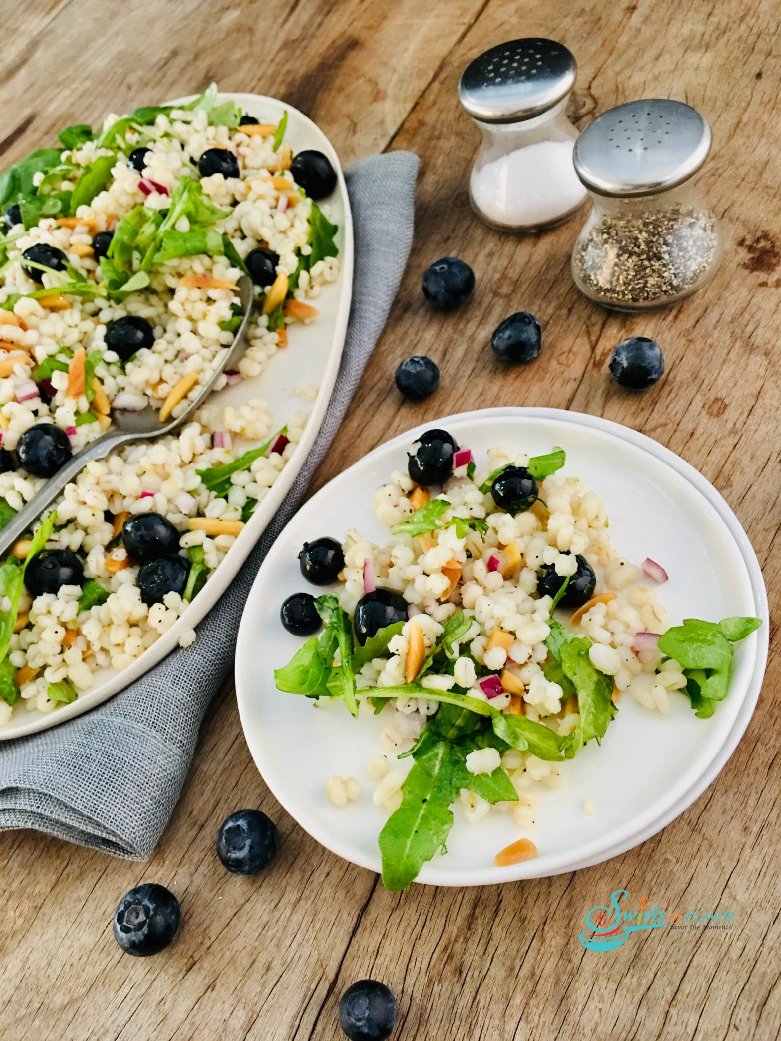 overhead photo of barley salad with baby greens and blueberries