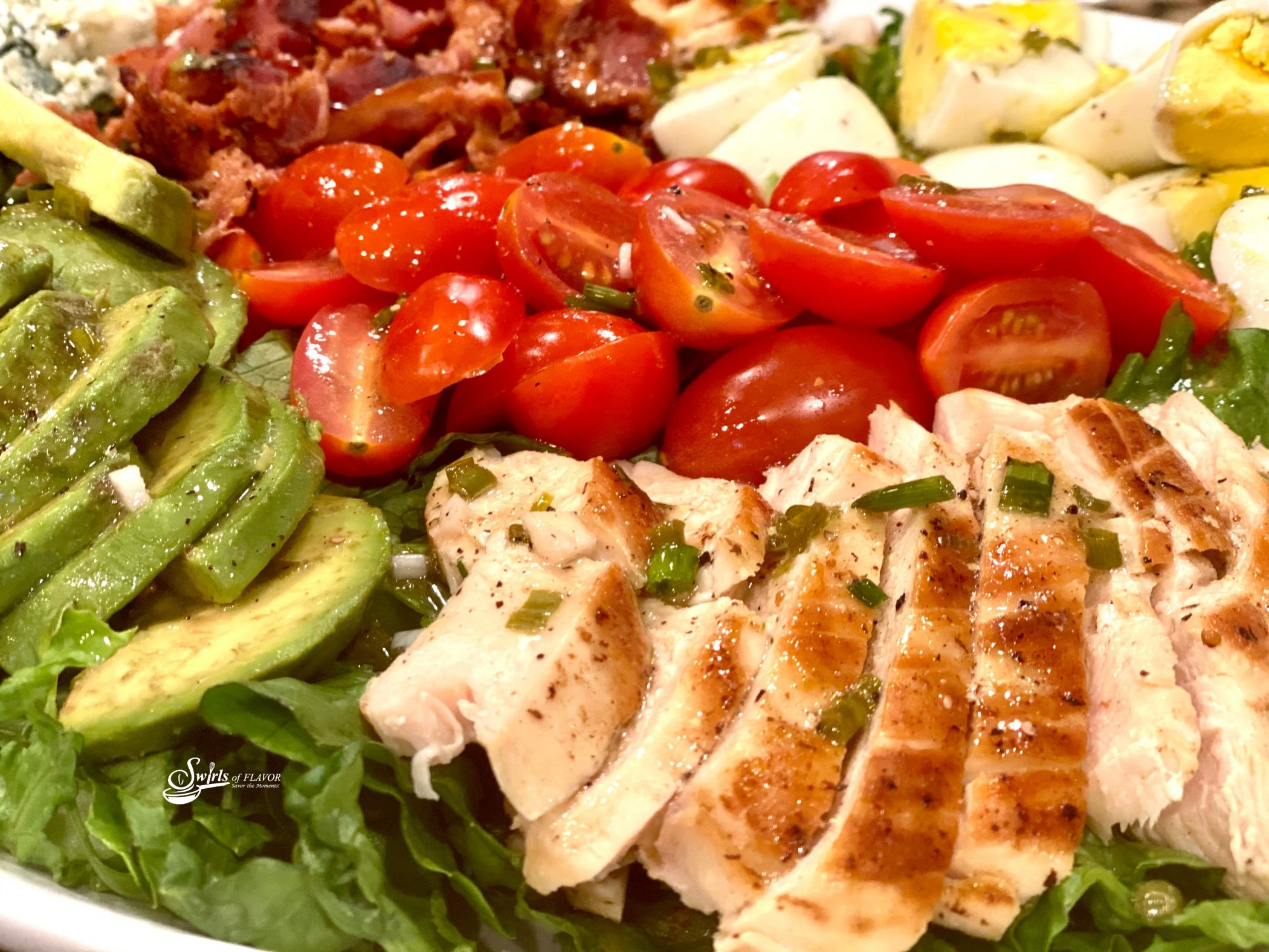 Close up of ingredients in a Cobb Salad, chicken, avocado, tomatoes, bacon and eggs