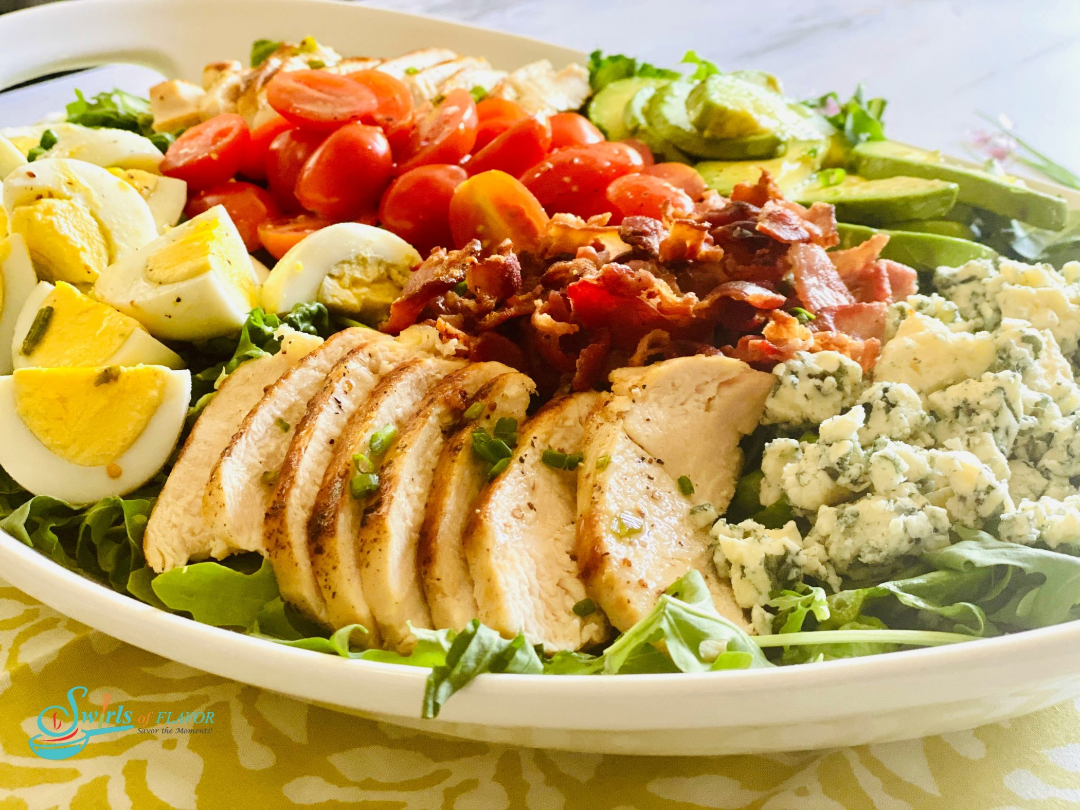 White oval platter filled with a Cobb Salad