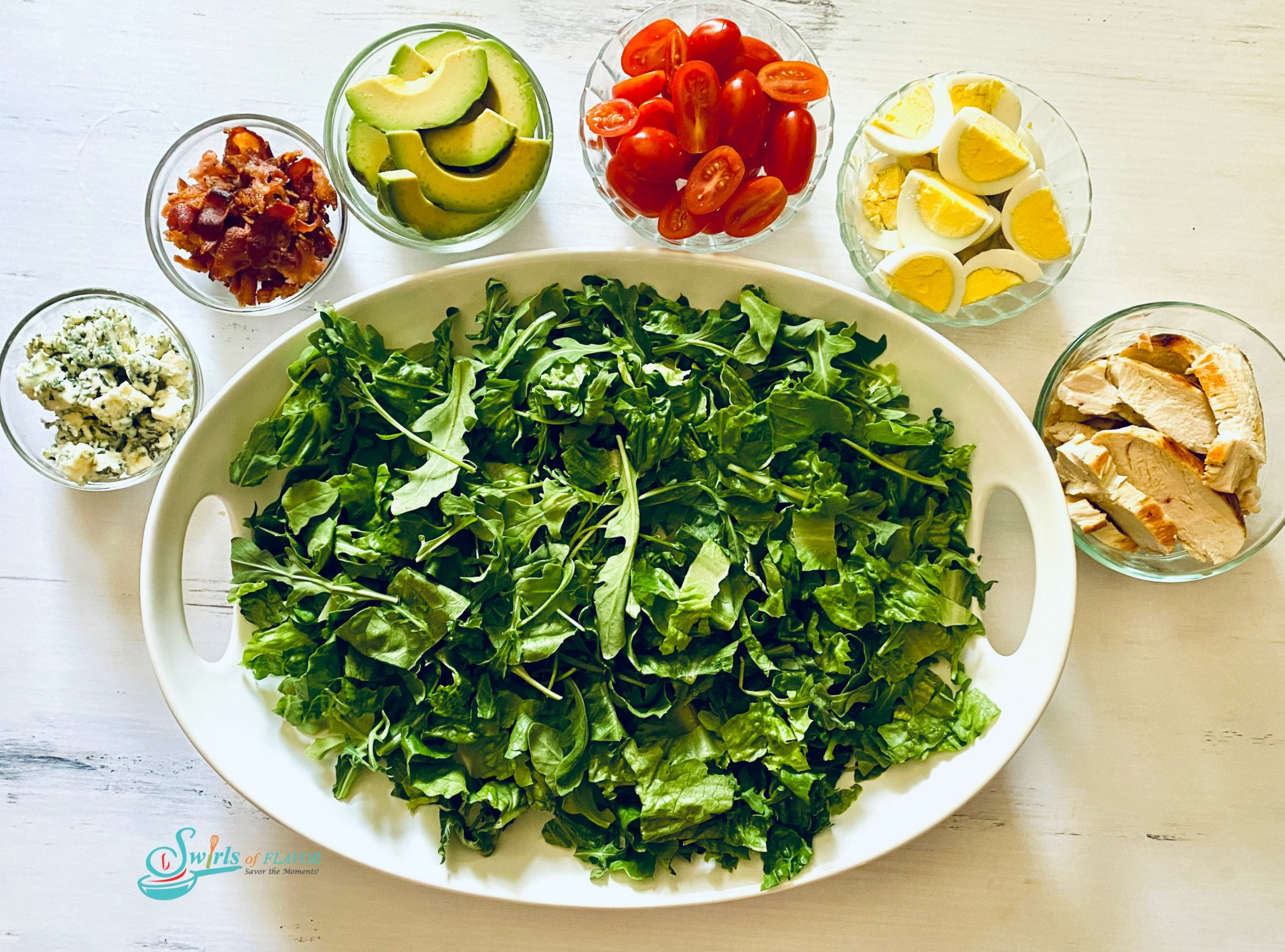 Large oval platter filled with chopped greens and small bowls of Cobb Salad ingredients