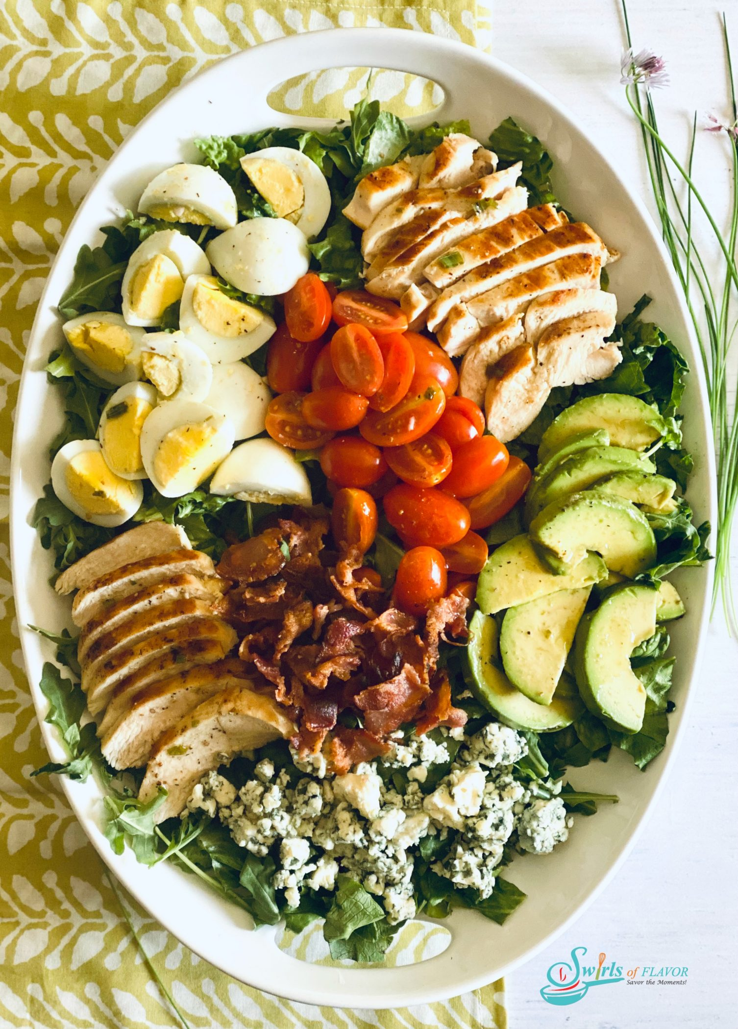 Overhead photo of a Cobb Salad in white oval platter on a green and white napkin with fresh chives