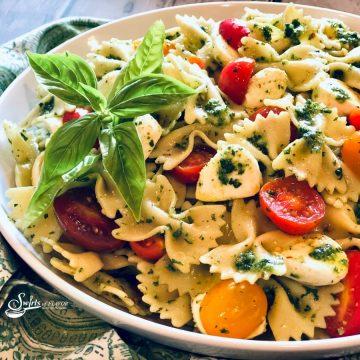 bowl of pasta salad with tomatoes, pesto and mozzarella