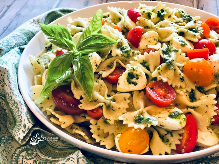 pasta salad with tomatoes and mozzarella in round bowl with fresh basil leaves and pesto