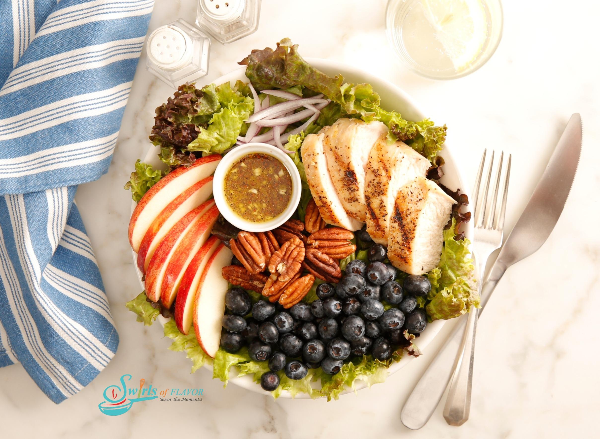 Arranged salad of chicken, blueberries, apples and honey mustard salad dressing