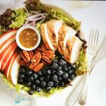 Apples, chicken, blueberries and pecans arranged on bed of greens with honey mustard salad dressing