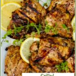 grilled chicken thighs with lemon slices and fresh oregano sprigs and text overlay