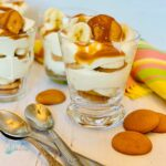 Glasses with layered banana , cookies and bananas with spoons and napkinguddin