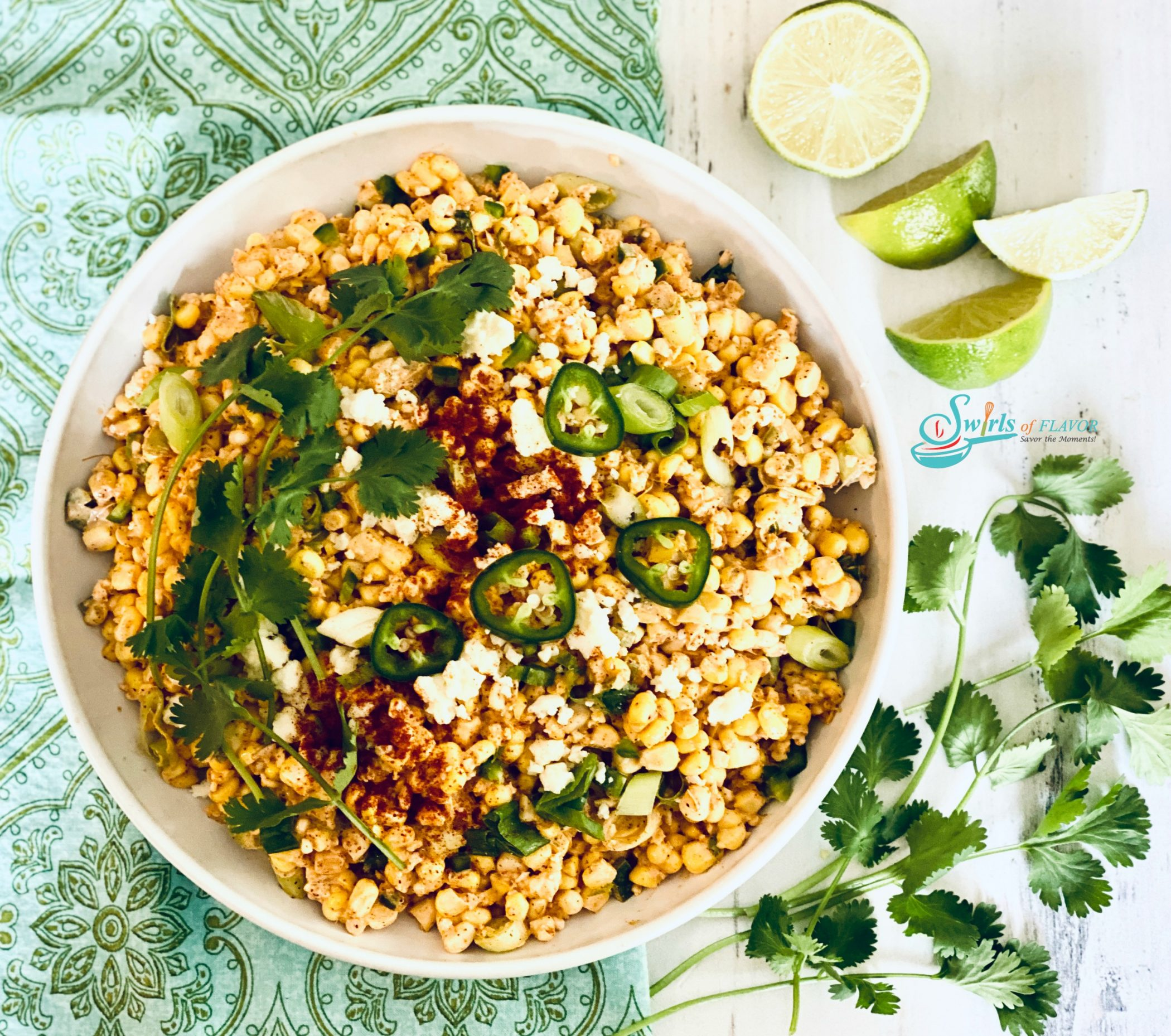 corn, jalapeno, cheese and cilantro in bowl with fresh limes