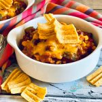 bowls of beef chili with corn chip topping