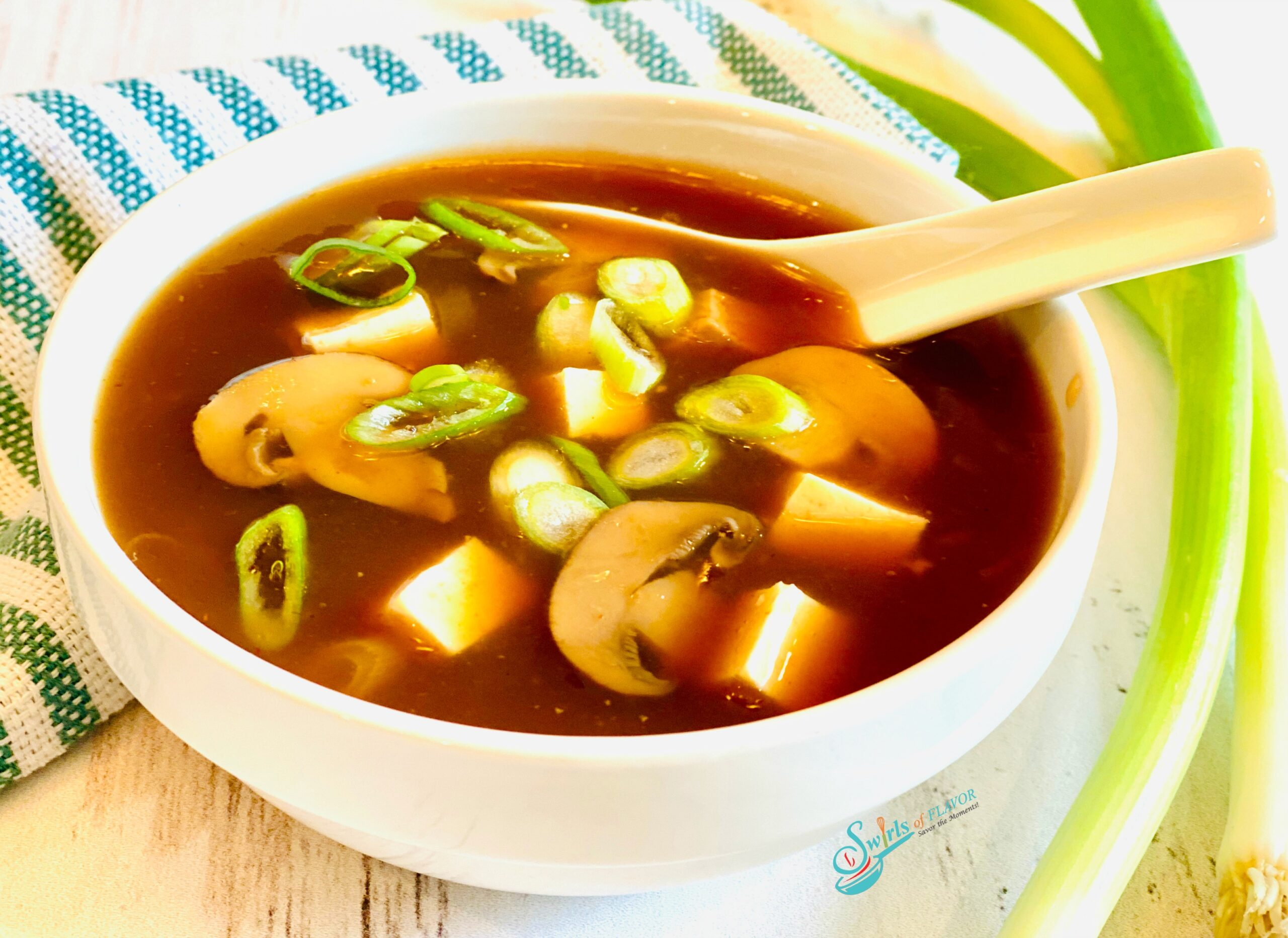 homemade hot and sour soup in white bowl with spoon