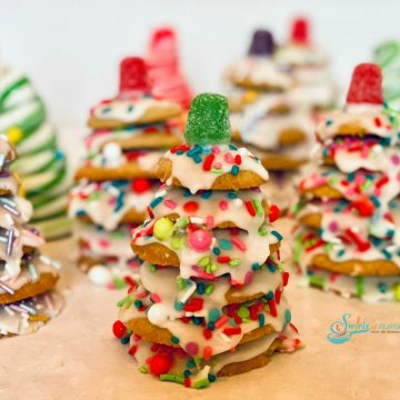 many stacked cookie Christmas trees with sprinkles and candy