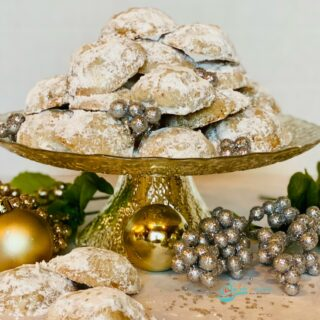 cake stand with pile of cookies with confectioners' sugar and oranments