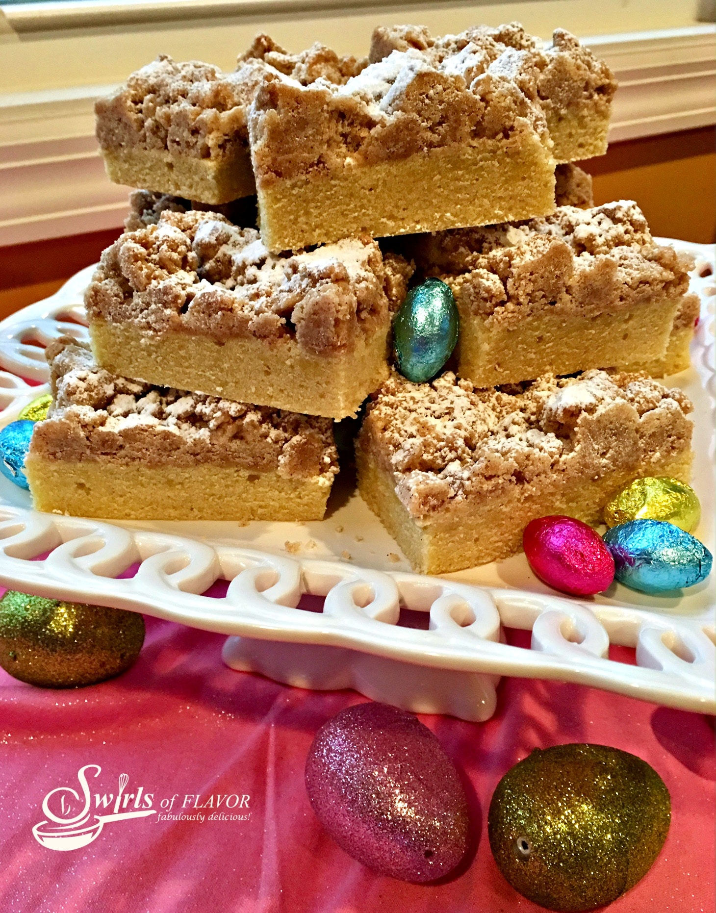crumb cake pieces stacked on white platter with chocolate Easter egg candy