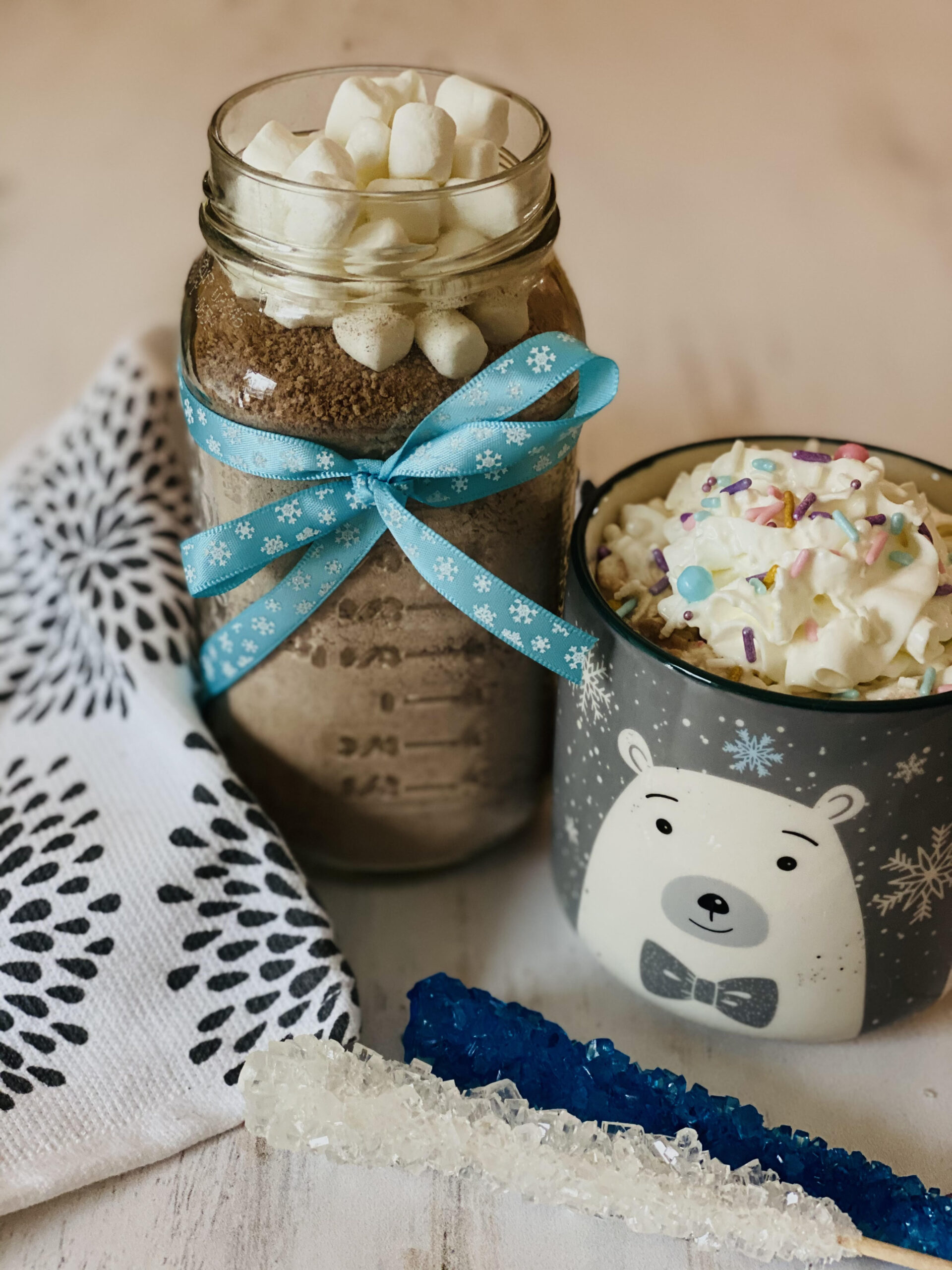hot chocolate mix in jar with mug of hot chocolate and whipped cream