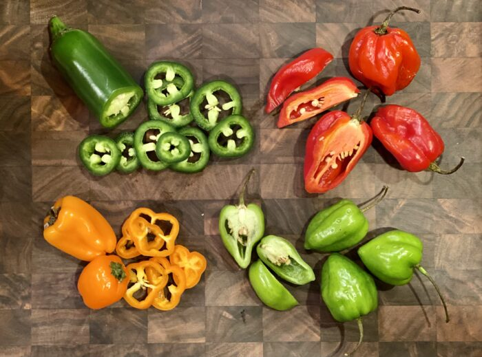 assorted fresh hot peppers on cutting board