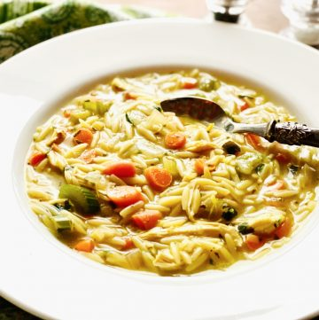 chicken orzo soup in white soup bowl with spoon