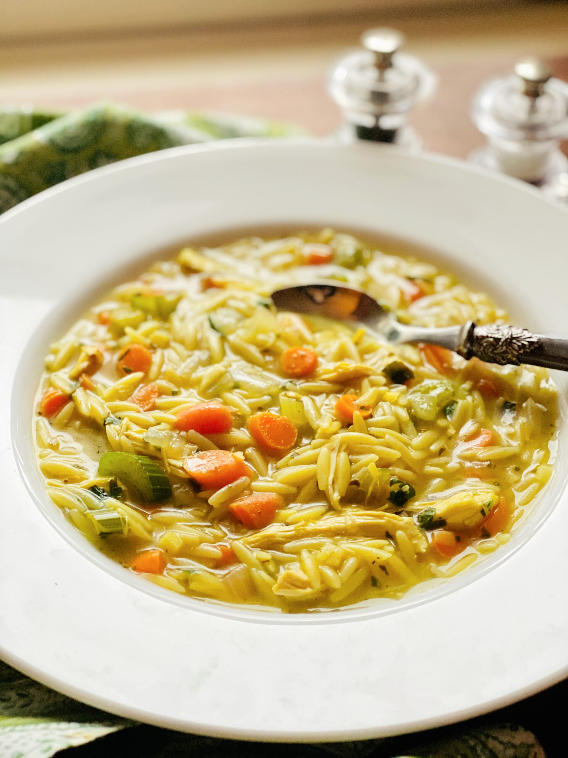 bowl of chickne orzo soup with spoon and salt and pepper shakers
