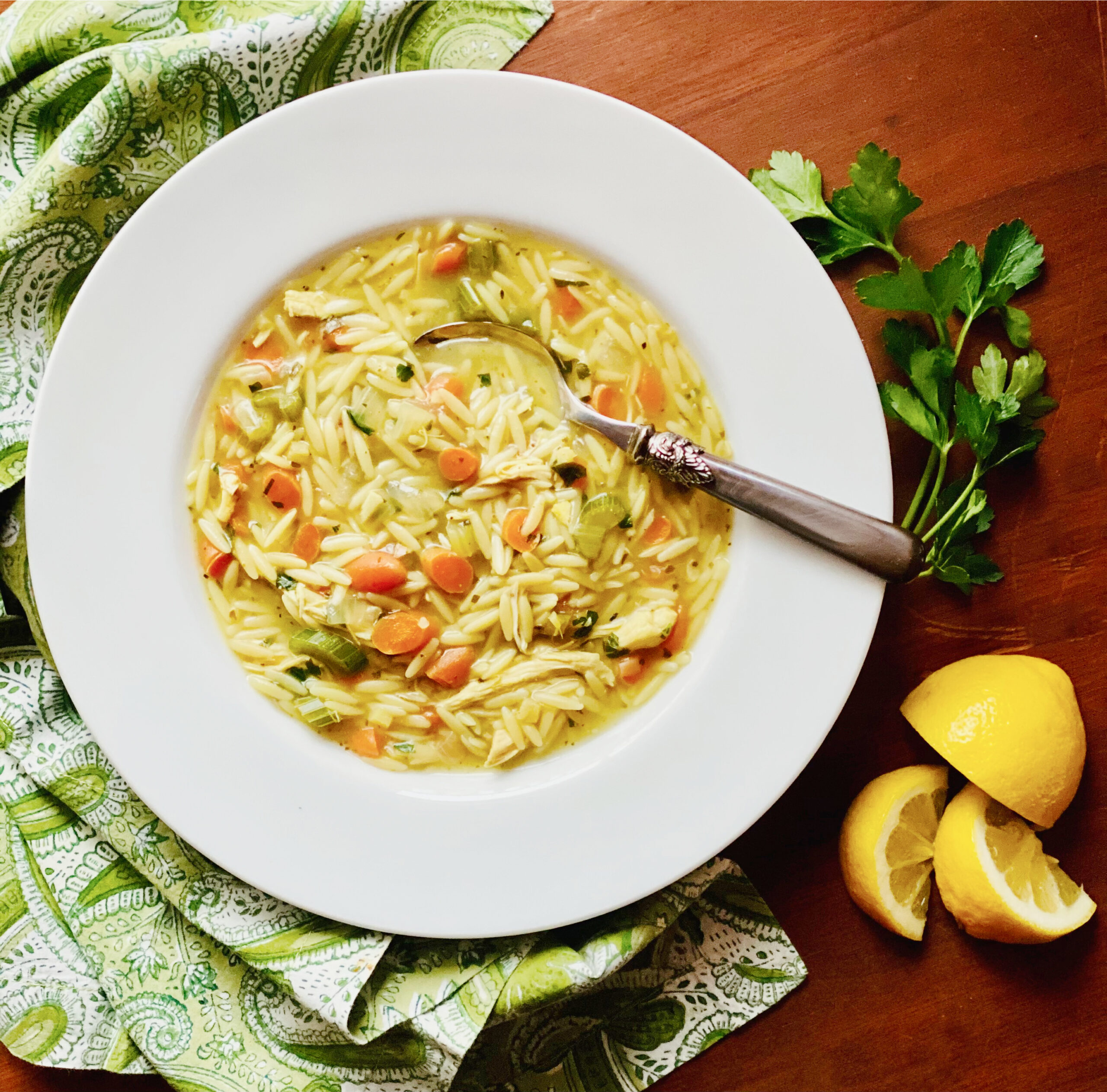 bowl of Chicken Orzo Soup with spoon, green napkin, lemon and parsley