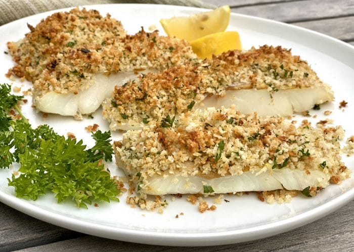 baked cod on platter with parsle and lemon wedges