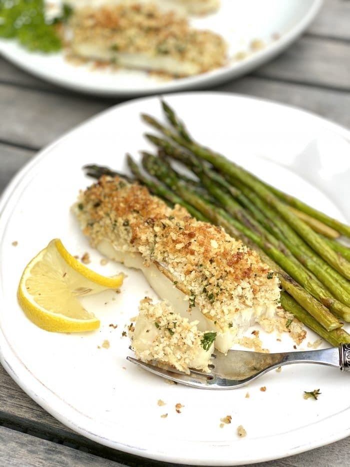 single serving of panko crusted cod with asparagus on white plate