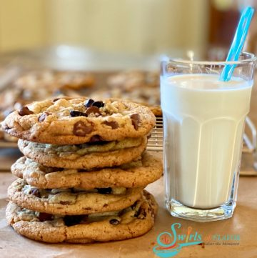 stack of Brown Butter Cookies With Espresso Chips and a glass of mik with a straw