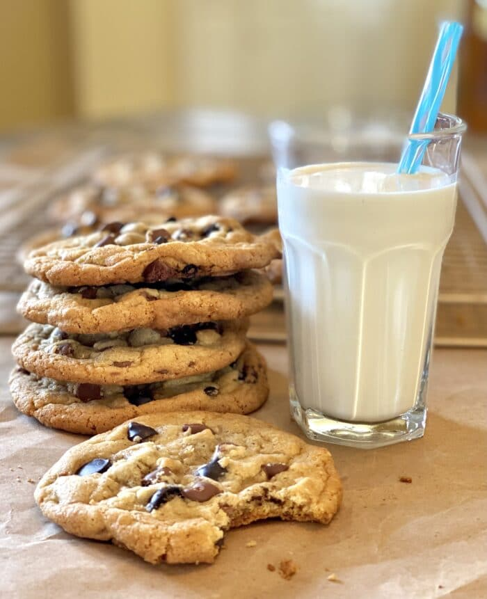 Stack of Brown Butter Cookies With Espresso chips and a glass of milk with a straw