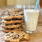 stack of brown butter cookies with glass of milk and a straw