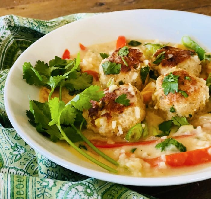four chicken meatballs with bell peppers, rice and coconut sauce in white bowl