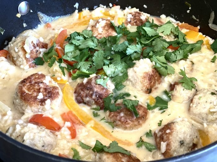 Top cooked chicken meatballs with cilantro