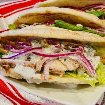 close up of a chicken gyro sandich on pita bread