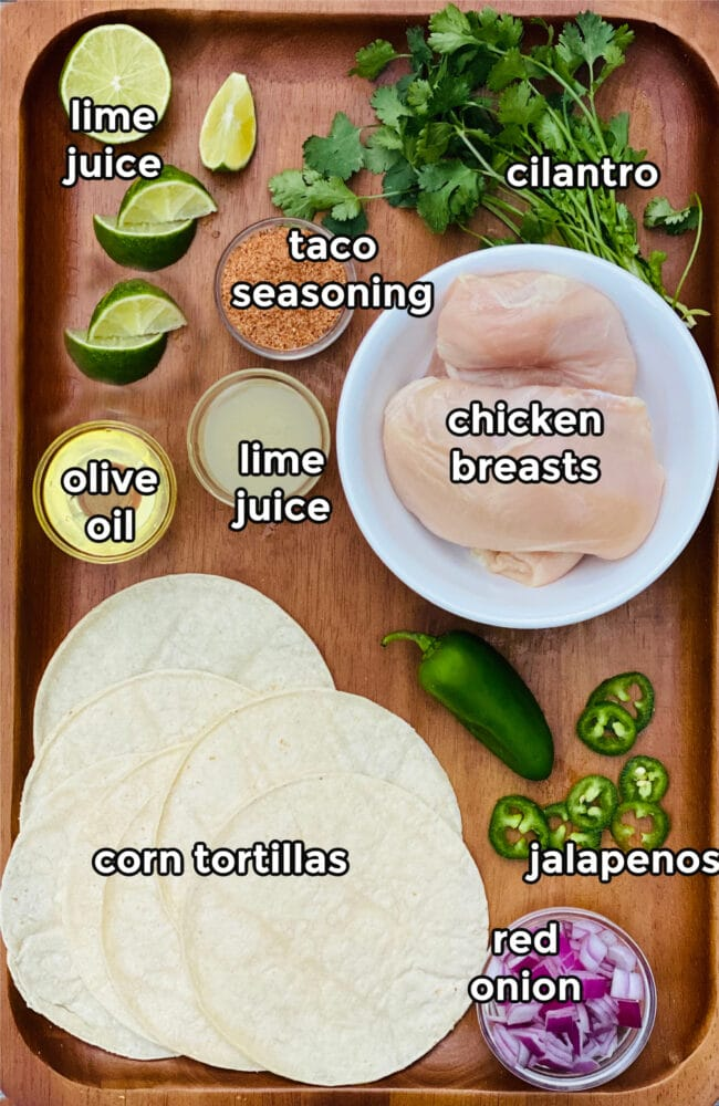 ingredients for chicken street tacos on a wooden board