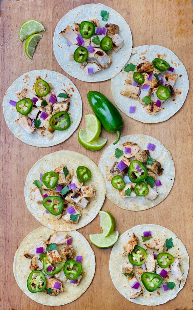 chicken street tacos on wooden board with lime wedges and jalapeno