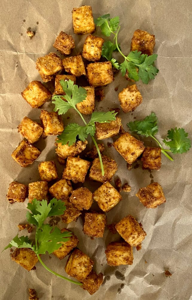 crispy tofu on parchment paper with cilantro sprigs