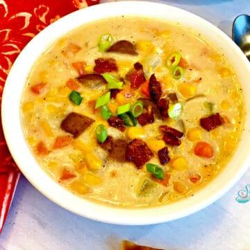 bowl of potato corn chowder with red print napkin