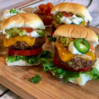 Jalapeno Cheddar Burgers with toppings on wooden board