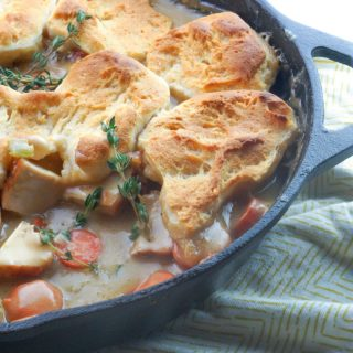 chicken pot pie in a cast iron skillet with one scoop out