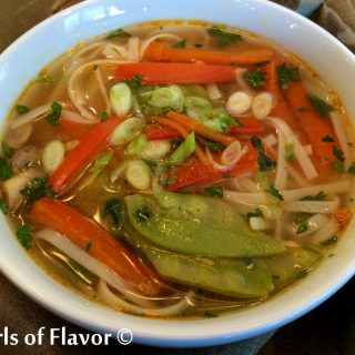 white bowl of Thai ginger soup with fresh vegetables